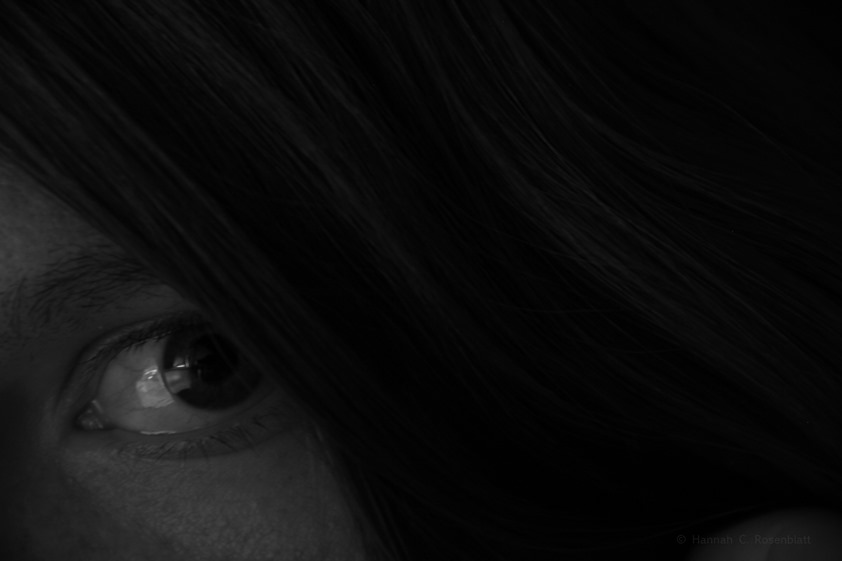 waagererechtes Schwarz-Weißfoto. drei Viertel der Fläche sind Haare (dunkler Grund mit hellen Strähnen drauf) die von oben links nach unten rechts in sachten Wellenlinien verlaufen. im unten linken Viertel ist der Gesichtsbereich mit einem offenen Auge, dessen Iris nach oben rechts gerichtet ist