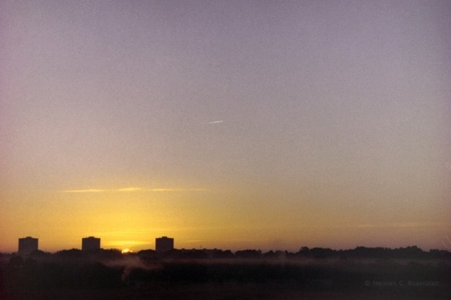 ein waagerechtes Farbfoto von einem Sonnenaufgang - unteres Viertel im Dunklen, durchzogen von weißen Nebellinien in Hellem rot-lila-weiß, im Vietel darüber ein Gelb in mehreren Facetten um die Sonne von der nur wenig zu sehen ist, im Viertel darüber eine kleine Linie von einem Düsenflieger, im Viertel darüber nur noch blau-lila Himmel